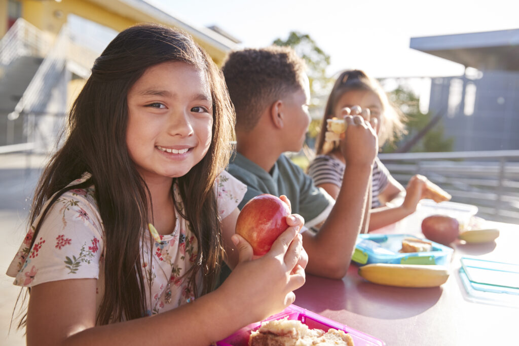 Girl at elementary school lunch table smiling to camera